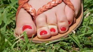 Red Toes Close Up On The Grass by Feetatjoes
