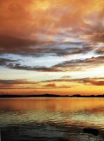 Orange sky above calm water by wellgraphic