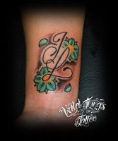 Letters and flowers on wrist by WildThingsTattoo