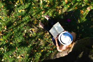 Woman sitting and reading under a tree by DWaschnigPhotography