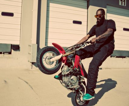 A black man doing a wheelie on a tiny motorcycle. by cKlos